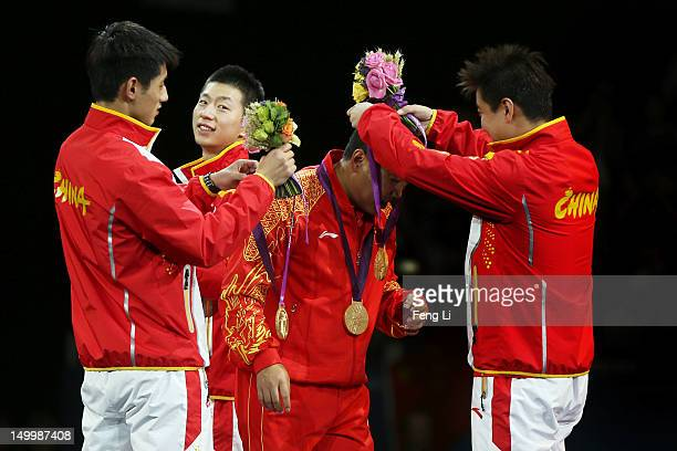 Gold medalists Ma Long Wang Hao and Zhang Jike of China celebrate with their coach Liu Guoliang by putting their medals around his neck during the...