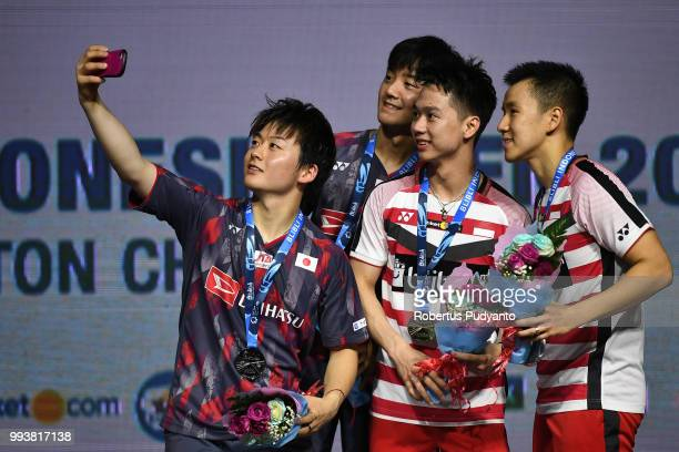 Gold medalists Marcus Fernaldi Gideon and Kevin Sanjaya Sukamuljo of Indonesia and silver medalists Takuto Inoue and Yuki Kaneko of Japan take a...
