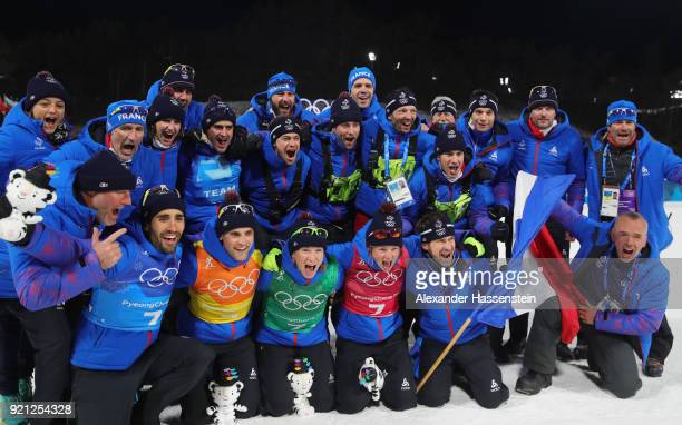 Gold medalists Marie Dorin Habert Anais Bescond Simon Desthieux and Martin Fourcade of France celebrate with their team after the victory ceremony...
