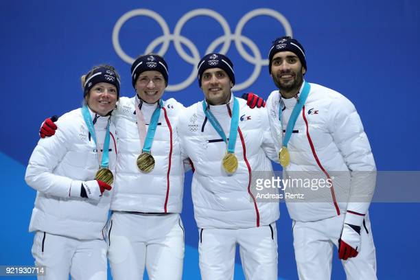 Gold medalists Marie Dorin Habert Anais Bescond Simon Desthieux and Martin Fourcade of France celebrate during the medal ceremony for the Biathlon...