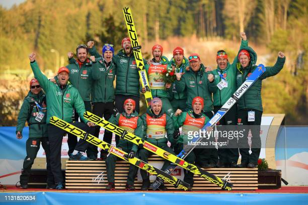 Gold medalists Markus Eisenbichler Karl Geiger Richard Freitag and Stephan Leyhe of Germany pose for a photo with their team following their victory...