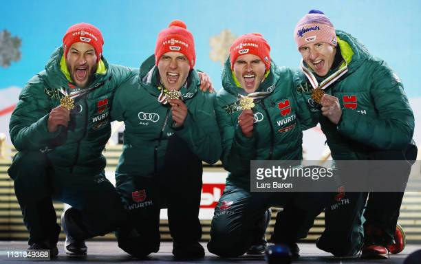 Gold medalists Markus Eisenbichler Karl Geiger Richard Freitag and Stephan Leyhe of Germany pose with the medals during the medal ceremony for the...