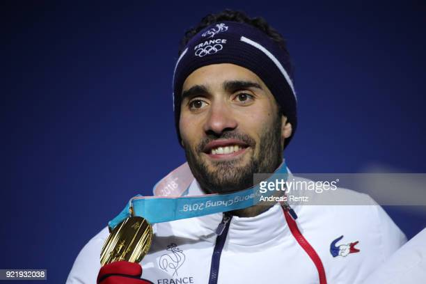 Gold medalists Martin Fourcade of France celebrates with his team during the medal ceremony for the Biathlon 2x6km Women 2x75km Men Mixed Relay on...