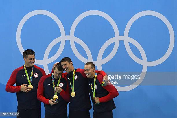 Gold medalists Nathan Adrian Ryan Held Michael Phelps and Caeleb Dressell of the United States celebrate on the podium during the medal ceremony for...
