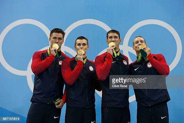 Gold medalists Nathan Adrian Ryan Held Michael Phelps and Caeleb Dressell of the United States kiss their medals on the podium during the medal...