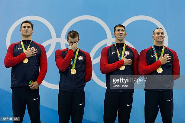 Gold medalists Nathan Adrian Ryan Held Michael Phelps and Caeleb Dressell of the United States sing the national anthem on the podium during the...