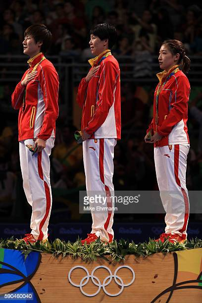 Gold medalists Ning Ding, Xiaoxia Li and Shiwen Liu of China pose on the podium during the medal ceremony for the Women's Team Match between China...