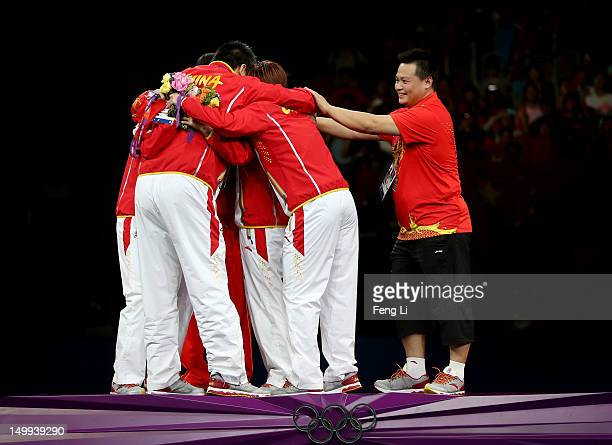 Gold medalists Ning Ding Yue Guo and Xiaoxia Li of China celebrate with their coaches on the podium during the medal ceremony for the Women's Team...