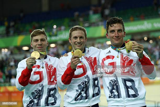 Gold medalists Philip Hindes Jason Kenny and Callum Skinner of Great Britain celebrate on the podium after winning the Men's Team Sprint Track...