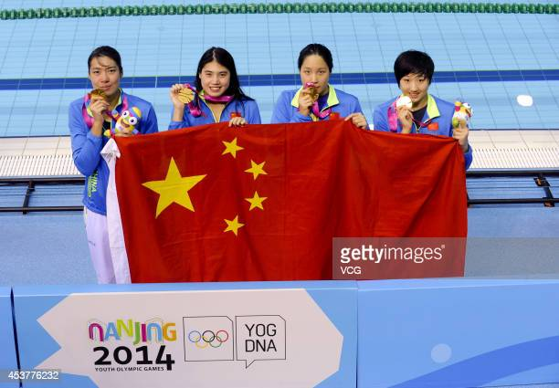 Gold medalists Qiu Yuhan He Yun Zhang Yufei and Shen Duo of China celebrate on the podium after the Women's 4x100m Medley Relay final match on day...