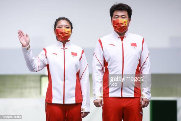 Gold medalists Ranxin Jiang and Wei Pang of Team China celebrate on the podium after the 10m Air Pistol Mixed Team Gold Medal Match on day four of...