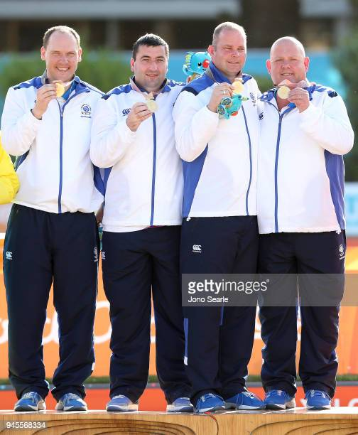 Gold Medalists Ronald Duncan Derek Oliver Paul Foster and Alexander Marshall of Scotland pose during the medal ceremony after winning the gold medal...