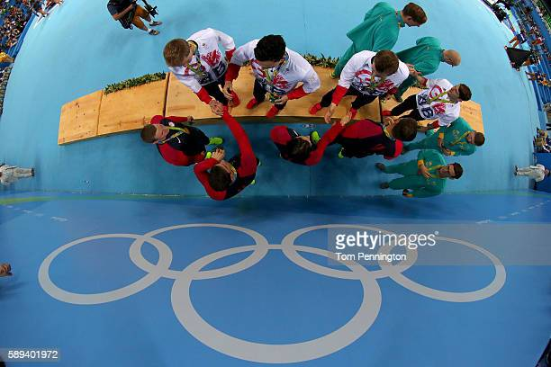 Gold medalists Ryan Murphy Cody Miller Michael Phelps and Nathan Adrian of the United States congratulate Team Great Britain on the podium during the...