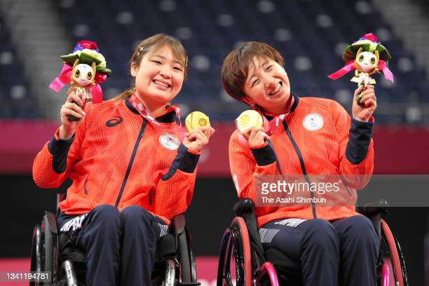 Gold medalists Sarina Satomi and Yuma Yamazaki of Team Japan celebrate on the podium at the medal ceremony for the Badminton Women's Doubles WH on...