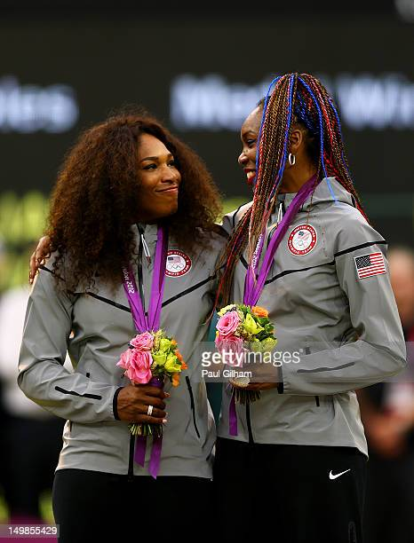 Gold medalists Serena Williams of the United States and Venus Williams of the United States celebrate on the popdium during the medal ceremony for...
