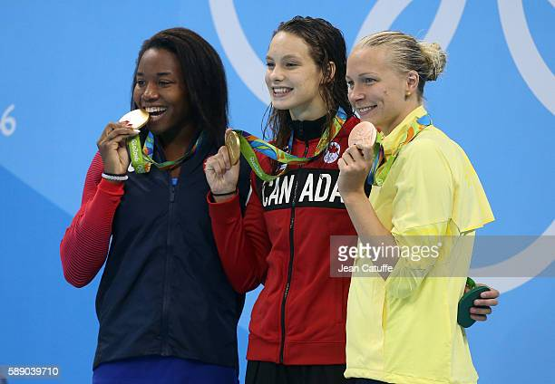 Gold medalists Simone Manuel of USA and Penny Oleksiak of Canada and bronze medalist Sarah Sjostorm of Sweden pose during the medal ceremony for the...