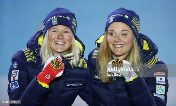Gold medalists Stina Nilsson of Sweden and Maja Dahlqvist of Sweden celebrate during the medal ceremony for the Ladies' Cross Country Team Sprint of...