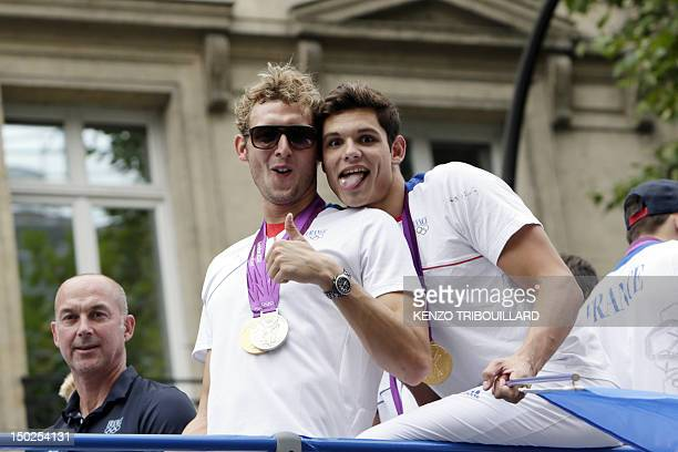 Gold medalists swimmers Amaury Leveaux and Florent Manaudou celebrate on top of a double decker bus surrounded by supporters during the French...