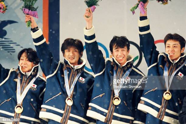 Gold medalists Takanobu Okabe Hiroya Saito Masahiko Harada and Kazuyoshi Funaki of Japan celebrate on the podium at the medal ceremony for the Ski...