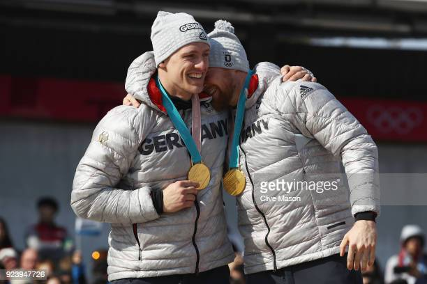 Gold medalists Thorsten Margis and Martin Grothkopp of Germany celebrate on the podium during the medal ceremony after the 4man Boblseigh Heats on...