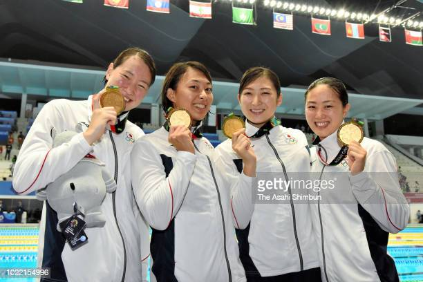Gold medalists Tomomi Aoki Satomi Suzuki Rikako Ikee and Natusmi Sakai of Japan pose for photographs after the medal ceremony for the Swimming...