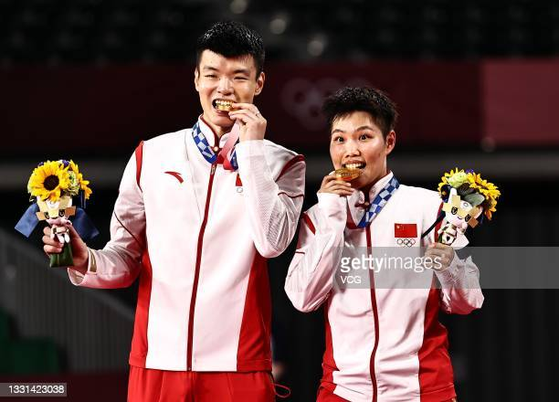 Gold medalists Wang Yilyu and Huang Dongping of Team China celebrate on the podium after the Mix Doubles Gold Medal match on day seven of the Tokyo...
