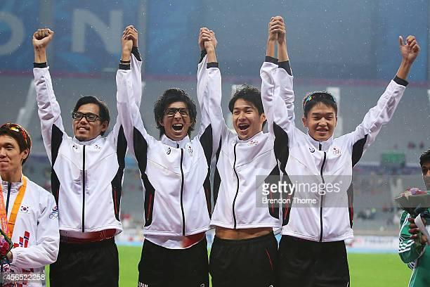 Gold medalists Yuzo Kanemaru Kenji Fujimitsu Shota Iizuka and Nobuya Kato of Japan celebrate atop the podium following the Men's 4x400m Relay Final...