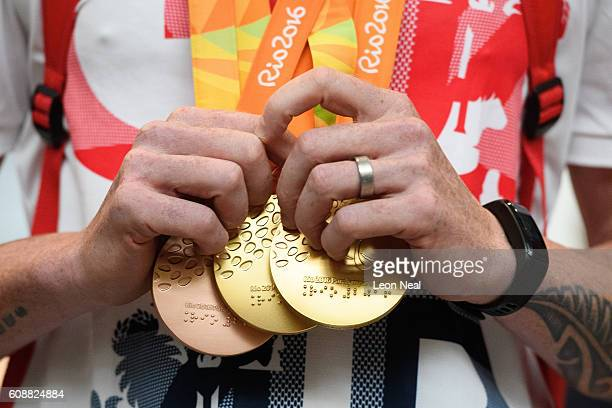 Gold medallist Adam Duggleby holds his medals after arriving on British Airways flight BA2016 from Rio de Janeiro to London Heathrow Terminal 5 on...