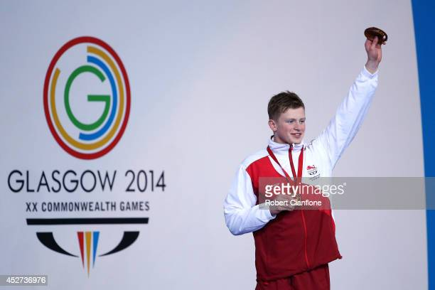 Gold medallist Adam Peaty of England celebrates during the medal ceremony for the Men's 100m Breaststroke Final at Tollcross International Swimming...