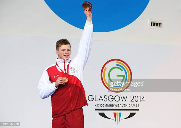 Gold medallist Adam Peaty of England poses during the medal ceremony for the Men's 100m Breaststroke Final at Tollcross International Swimming Centre...