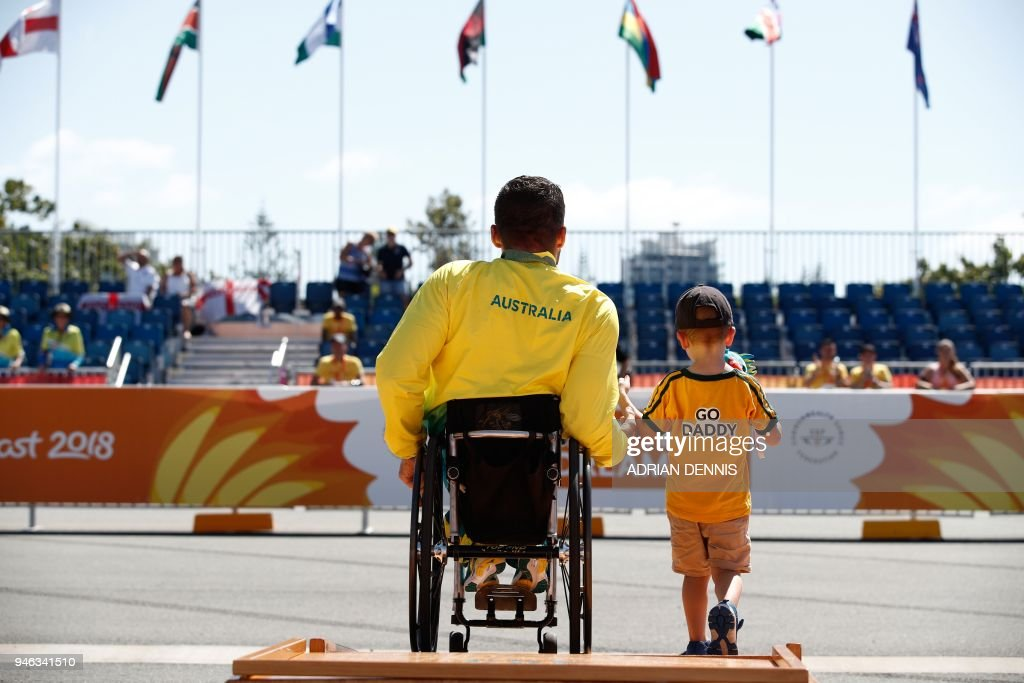 Gold medallist Australia's Kurt Fearnley and his son are seen on the podium after the medal ceremony for the athletics men's T54 marathon final during the 2018 Gold Coast Commonwealth Games at the Southport Broadwater Parklands venue on the Gold Coast on April 15, 2018. / AFP PHOTO / Adrian DENNIS