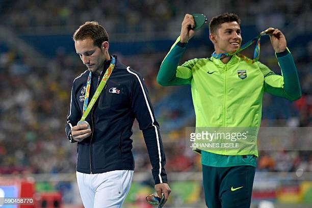 Gold medallist Brazil's Thiago Braz Da Silva and silver medallist France's Renaud Lavillenie attend the medal ceremony for the men's pole vault...