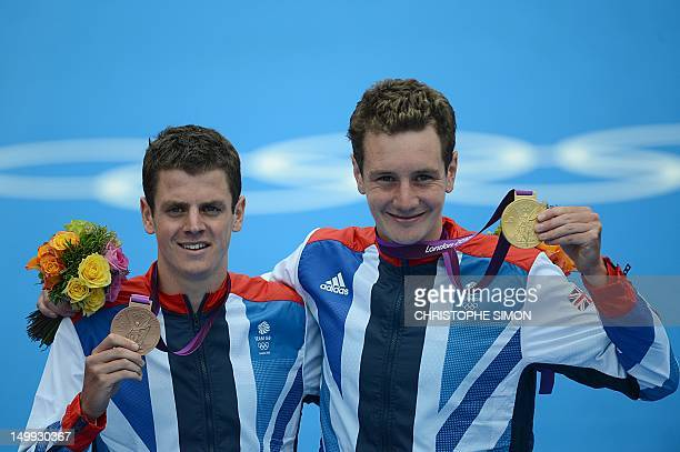 Gold medallist Britain's Alistair Brownlee and his brother bronze medallist Britain's Jonathan Brownlee celebrate on the podium of the men's...