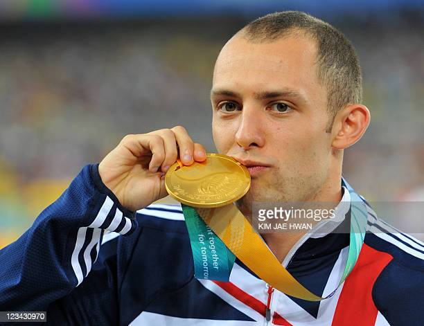 Gold medallist Britain's David Greene poses on the podium during the award ceremony for the men's 400 metres hurdles event at the International...