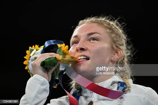 Gold medallist Britain's Lauren Price bites her medal as she celebrates on the podium during the victory ceremony for the women's middle boxing final...