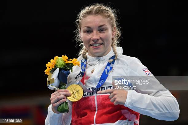 Gold medallist Britain's Lauren Price celebrates on the podium during the victory ceremony for the women's middle boxing final bout during the Tokyo...