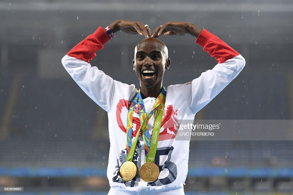 Gold medallist Britain's Mo Farah celebrates near the podium for the Men's 5000m during the athletics event at the Rio 2016 Olympic Games at the Olympic Stadium in Rio de Janeiro on August 20, 2016. / AFP / Eric FEFERBERG