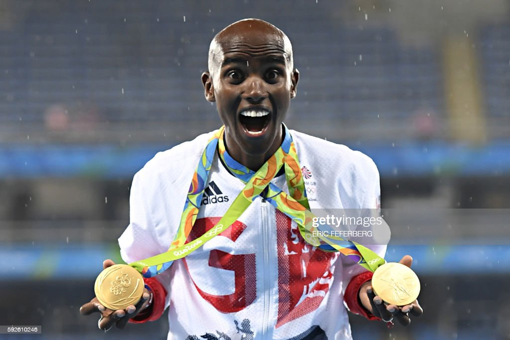 TOPSHOT - Gold medallist Britain's Mo Farah celebrates near the podium for the Men's 5000m during the athletics event at the Rio 2016 Olympic Games at the Olympic Stadium in Rio de Janeiro on August 20, 2016. / AFP PHOTO / Eric FEFERBERG