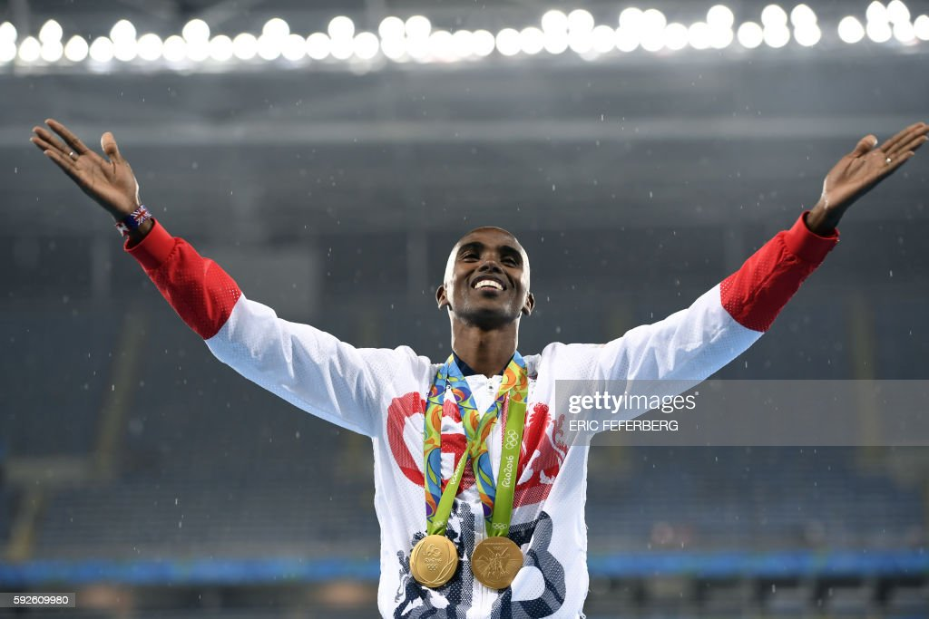 TOPSHOT - Gold medallist Britain's Mo Farah celebrates on the podium for the Men's 5000m during the athletics event at the Rio 2016 Olympic Games at the Olympic Stadium in Rio de Janeiro on August 20, 2016. / AFP PHOTO / Eric FEFERBERG
