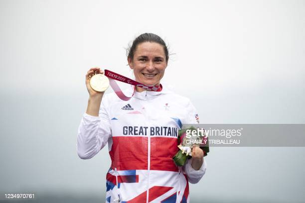 Gold medallist Britain's Sarah Storey celebrates on the podium after winning the women's cycling road individual C5 time trial during the Tokyo 2020...