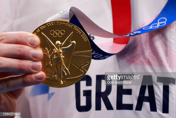 Gold medallist Britain's Tom Dean poses with his medal after the final of the men's 200m freestyle swimming event during the Tokyo 2020 Olympic Games...