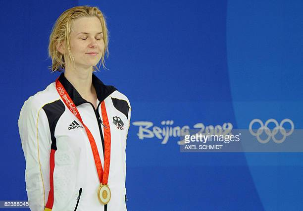 Gold medallist Britta Steffen of Germany stands on the podium during the women's 50m freestyle swimming final medal ceremony at the National Aquatics...