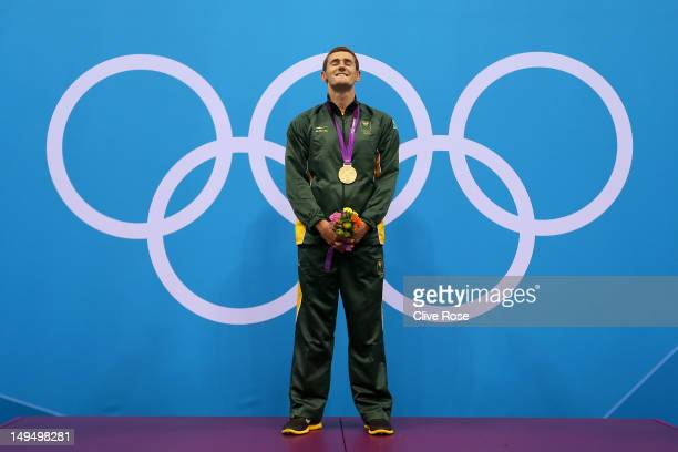Gold medallist Cameron van der Burgh of South Africa poses on the podium during the medal ceremony following the Men's 100m Breastsroke final on Day...