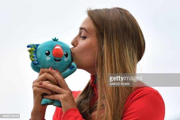 Gold medallist Canadas Alysha Newman kisses the game mascot Borobi during the medal ceremony for the athletics women's pole vault during the 2018...
