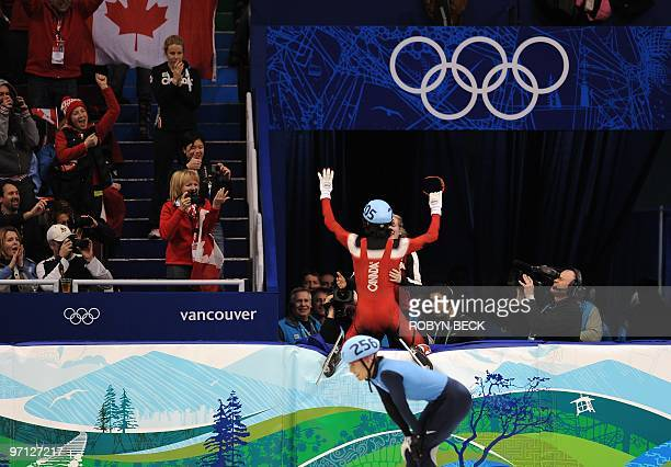 Gold medallist Canada's Charles Hamelin celebrates as disqualified US Apolo Anton Ohno is pictured on the ice rink at the end of the Men's 500 m...
