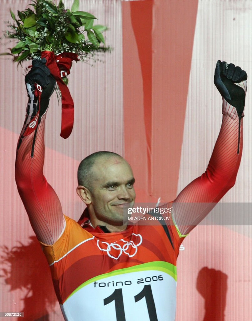 Gold medallist, Canadian slider Duff Gibson celebrates on the podium during the flower giving ceremony after the men's skeleton event at the Turin 2006 Winter Olympics in Cesana Pariol, 17 February 2006.