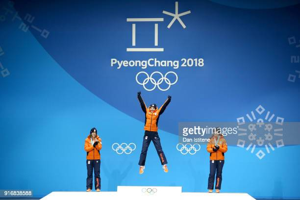 Gold medallist Carlijn Achtereekte of the Netherlands celebrates on the podium with silver medalist Ireen Wust of the Netherlands and bronze medalist...