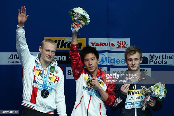 Gold medallist Chao He of China celebrates with silver medallist Ilia Zakharov of Russia and bronze medallist Jack David Laugher of Great Britain...
