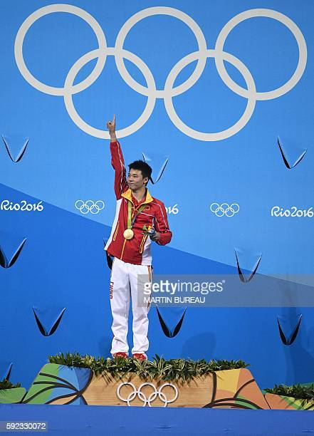 Gold medallist China's Chen Aisen celebrates during the podium ceremony of the Men's 10m Platform final during the diving event at the Rio 2016...