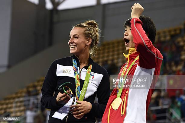 TOPSHOT Gold medallist China's Shi Tingmao and bronze medallist Italy's Tania Cagnotto react as Silver medallist China's He Zi receives a marriage...